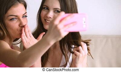 Two teenage girls taking selfie on phone, making self...