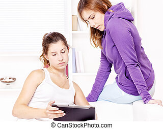 Two teenage girls using tablet computer
