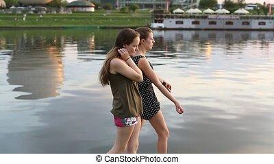Two teenage girls walking along the