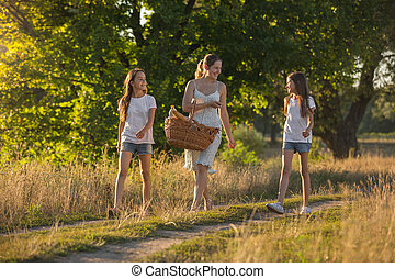 Two teenage girls walking with mother in field at sunset
