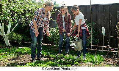 Two teenage girls watering garden at bright sunny day
