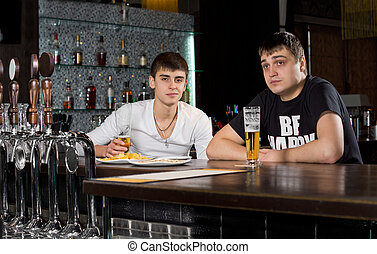 Two teenage men drinking at the pub - Two young teenage men...