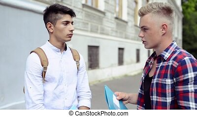 Two teenage students in front of university talking. - Two...