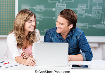 Two teenage students share a laptop in class