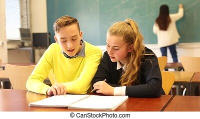 Two teenage students studying together in classroom. Education concept