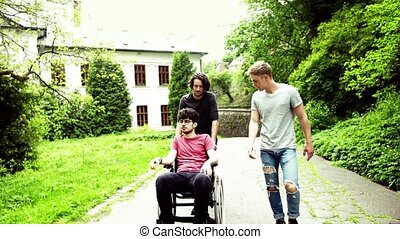 Two teenager boys with a disabled friend in wheelchair on a walk outside in town.