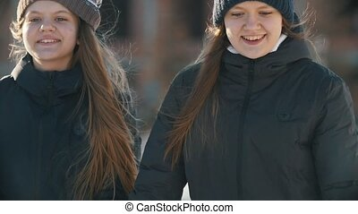 Two teenager girlfriends skating and holding each other hands