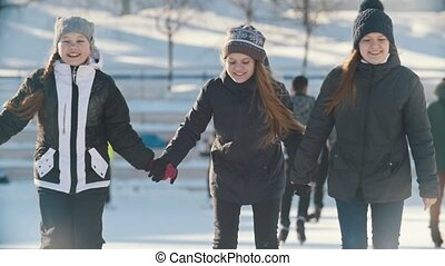 Two teenager girlfriends skating and holding each other...
