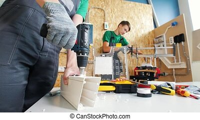 Two teenagers craftsmen drilling and sawing details in ...