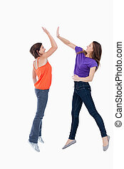 Two teenagers jumping while trying to join their hands
