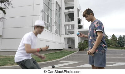 Two teenagers on street practicing new kendama moves
