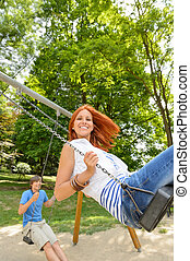 Two teenagers on swing playground in park