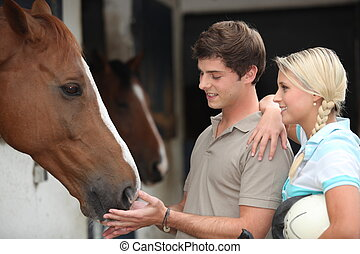 Two teenagers stood by horse stable
