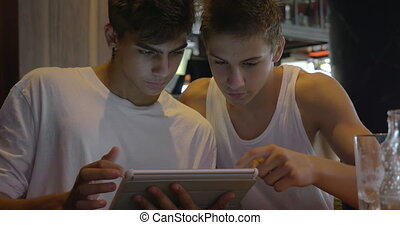 Two teenagers using tablet PC in cafe