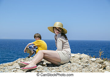 two teens sitting on the top of a mountain with blue ocean in background.