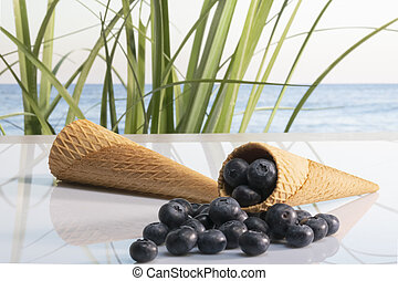 Two tempting ice cream cones with a bunch of delicious looking blueberries on a glass table