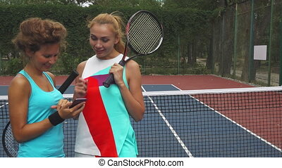 Two tennis girls discussing while sharing a smartphone