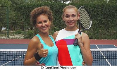 Two tennis girls smiling at camera
