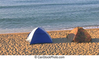 Two tents on a sandy beach