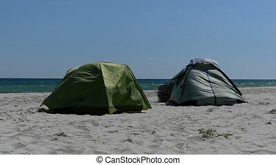 Two tents under bursts of wind on a sandy seacoast in slo-mo