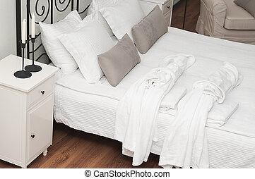 Two terry white dressing gowns on a bed in a bedroom