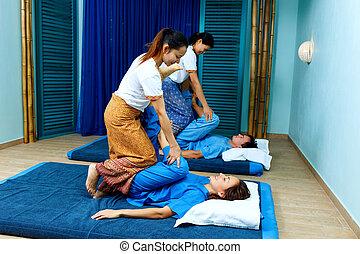 Two thai masseuses synchronously doing thai massage with yoga exercises.