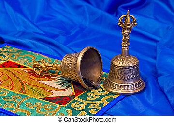 two Tibetan ritual bells on a blue background