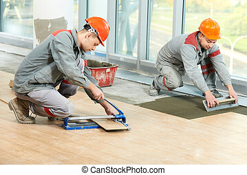 Two tilers at industrial floor tiling renovation - Two...