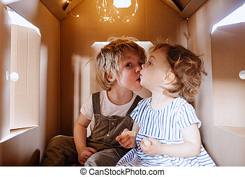 Two toddler children playing indoors in cardboard house at home, kissing.