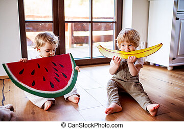 Two toddler children playing with large toy fruit indoors at home.