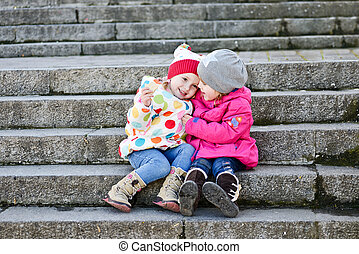 two toddler friends sitting on the stairs