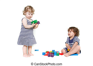 two toddler girls playing over white