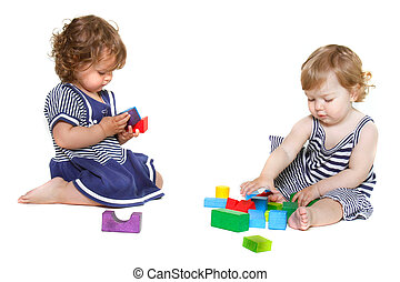 two toddler girls playing with building blocks over white