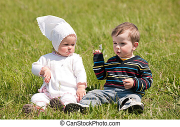 Two toddlers on the green grass