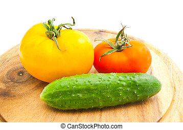 two tomatoes and cucumber on cutting board