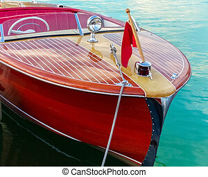 Two-toned classic wooden boat docked at side slip