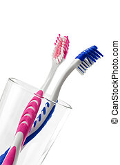 Two tooth brushes in glass. Isolated on white background