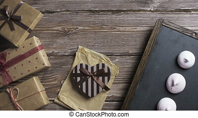 Two top view shots sequence, gift boxes over wooden desktop...