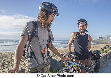 Two Touring Cyclists with Bicycles by Beach