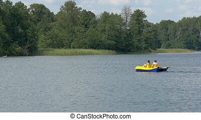 Two tourist paddling the water bicycle in the lake