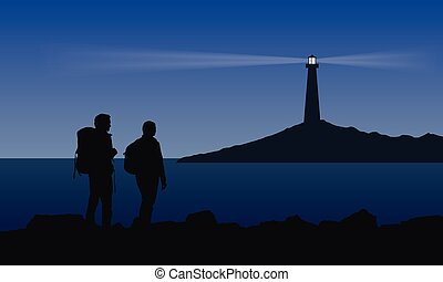 Two tourist with backpacks standing on the sea shore and watching the shining lighthouse on the island under blue night sky