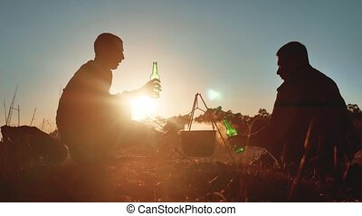 two tourists are beer sitting lifestyle by bonfire do selfie...