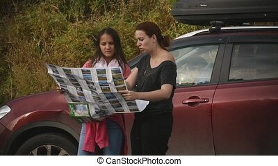 two tourists are looking for a road, studying the map of Altai during the trip