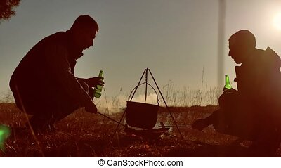 two tourists beer are sitting by bonfire hiking lifestyle...