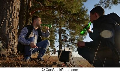 two tourists beer are sitting by bonfire hiking party in...