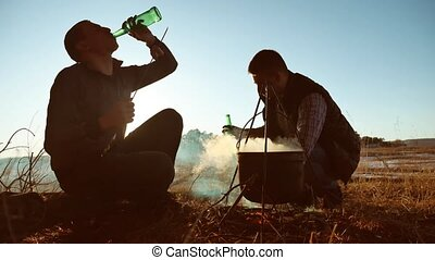 two tourists beer are sitting lifestyle by bonfire party in...