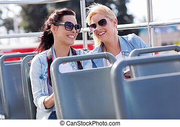 two tourists enjoying open top bus tour in the city