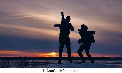two tourists happy silhouette travel at sunset climb the...