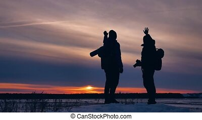 two tourists happy silhouette waving their farewell leaves...