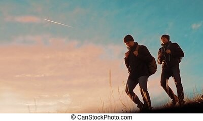 two tourists hikers men with backpacks at sunset go hiking trip. hikers adventure and the dog go walking. travel mountains lifestyle silhouette